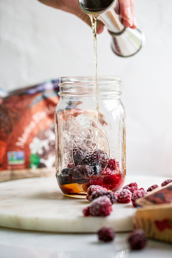 pouring whiskey into a glass jar with berries in it