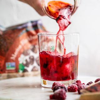 pouring a Blackberry Raspberry Old Fashioned from a jar into a glass