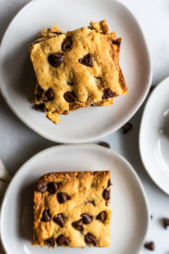 chocolate chip cookie bars on plates and a white background
