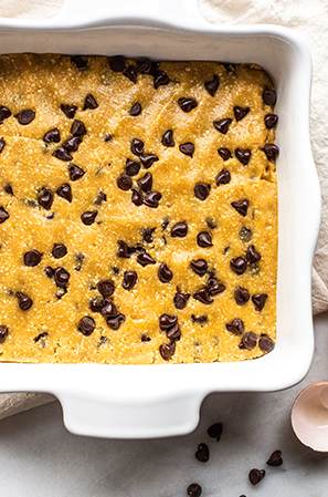 unbaked cookie bars in a white dish