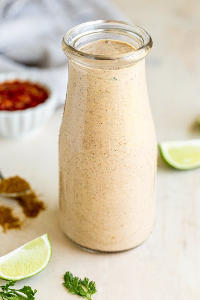 healthy taco lime dressing with greek yogurt in a glass with limes and a small bowl of salsa