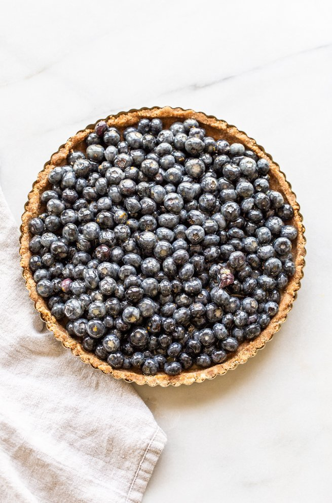 unbaked paleo blueberry tart on a white background