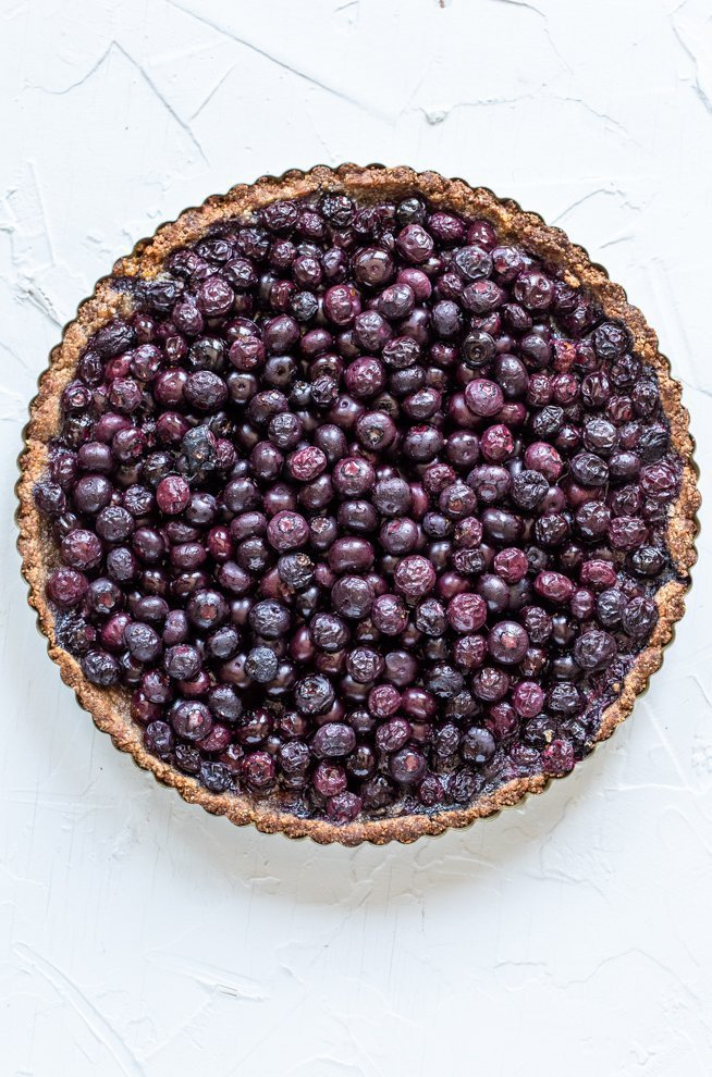 paleo blueberry tart on a white background
