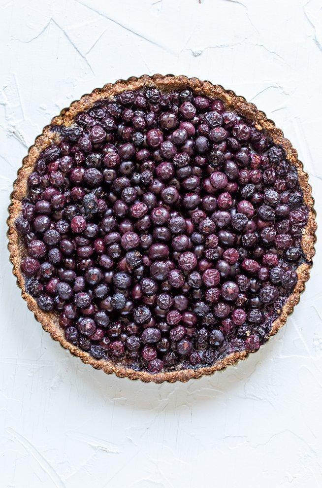 paleo blueberry tart on a white background
