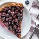 a slice of paleo blueberry tart on a white background