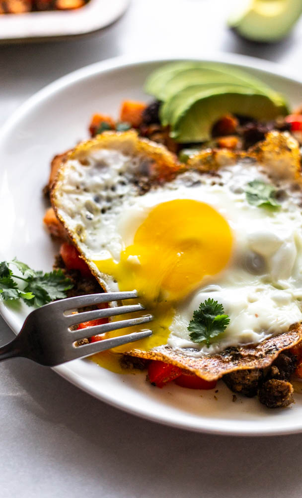 Looking for a better for you hash for breakfast (or whenever)? This Whole30 Bison Sweet Potato Hash has crispy sweet potatoes and veggies, lean bison and the perfect blend of spices. You can top with fried eggs, avocado, and cilantro for the best brunch or breakfast. This lower carb version can be made with turkey, beef, or venison, too. You make it on the stovetop and crisp it in the oven for the perfect potato. This recipe is #whole30approved and #paleo. #healthy #healthyrecipe #paleofood #breakfast