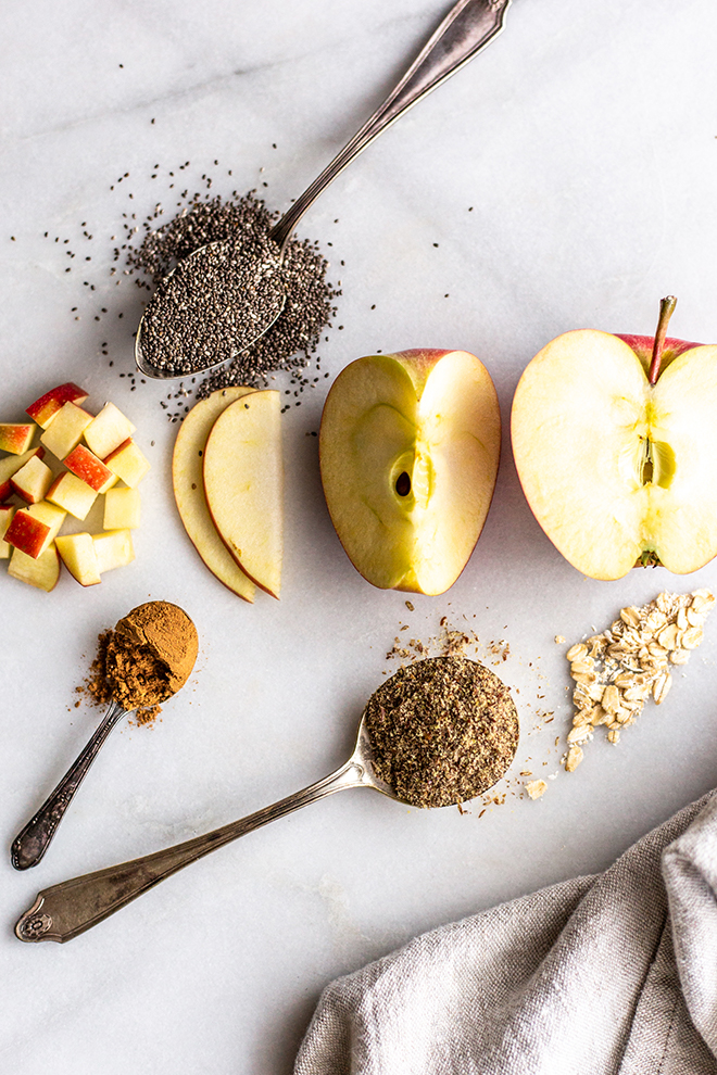 apples sliced and dices with chia seeds flax seeds and oats on a white background