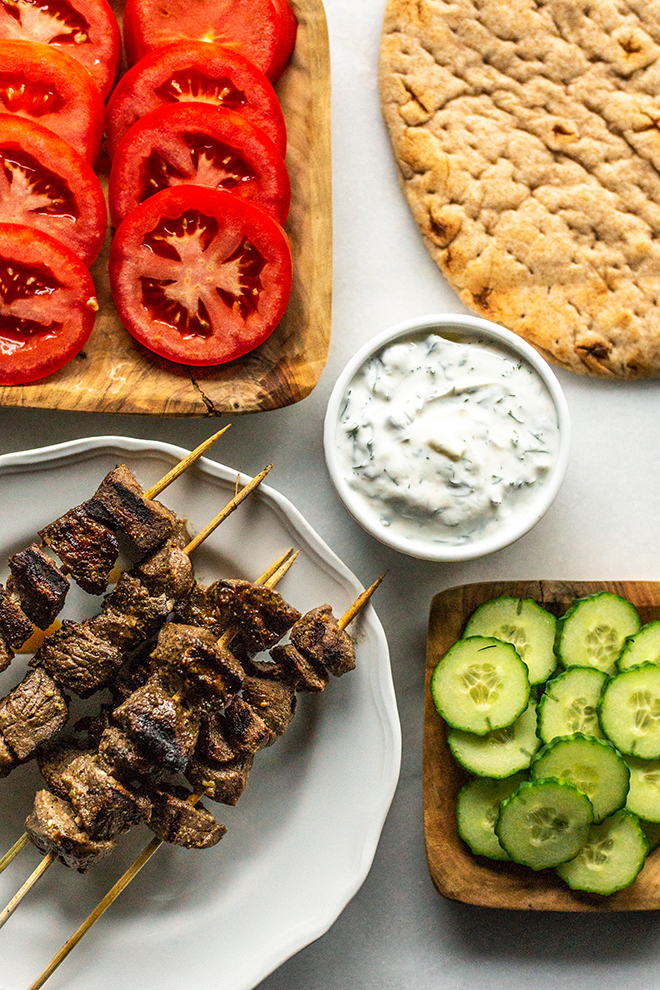 tomatoes, flatbread, tzatziki sauce, cucumber and grilled venison on a white background
