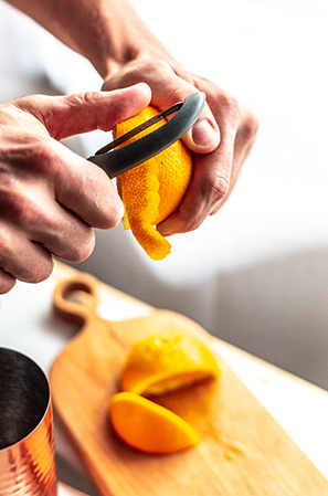 peeling an orange with a grey vegetable peeler
