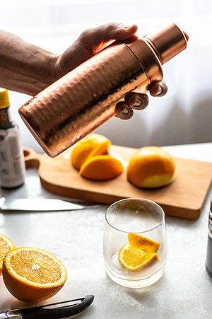 shaking an old fashioned cocktail with bourbon glasses, oranges and a wood cutting board