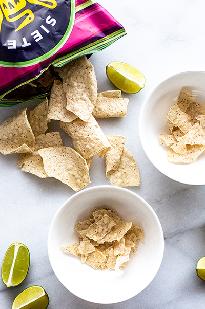 tortilla chips spilling out of a bag into a bowl