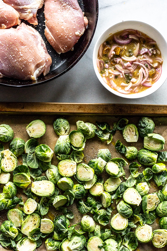 ingredients for chicken thighs and Brussels sprouts in a skillet and a sheet pan