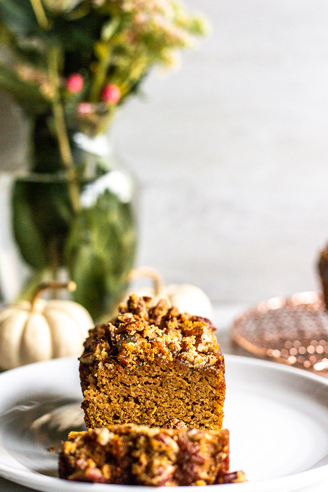 paleo pumpkin bread with crumble topping on a white plate with white pumpkins