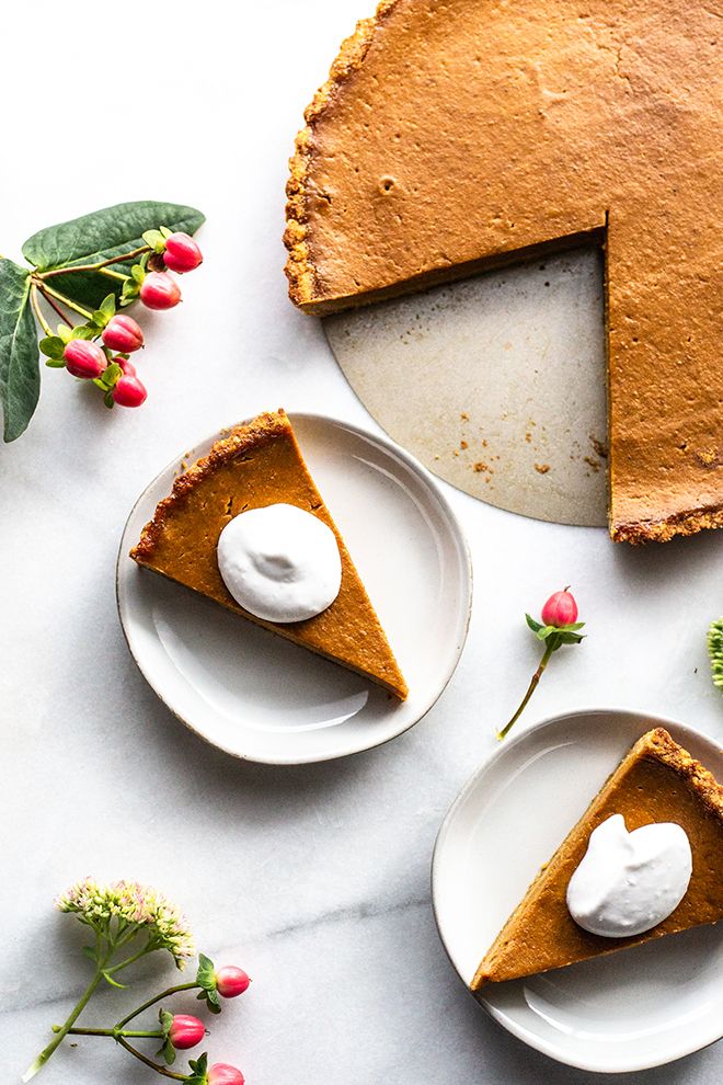 paleo pumpkin tart sliced on plates with whipped cream on a white background and flowers