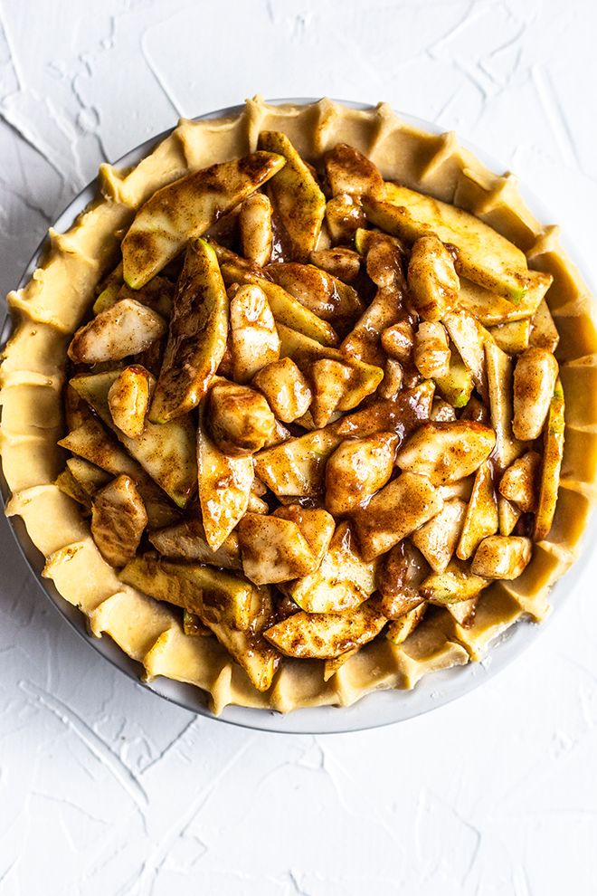 unbaked apple pear pie on a white background