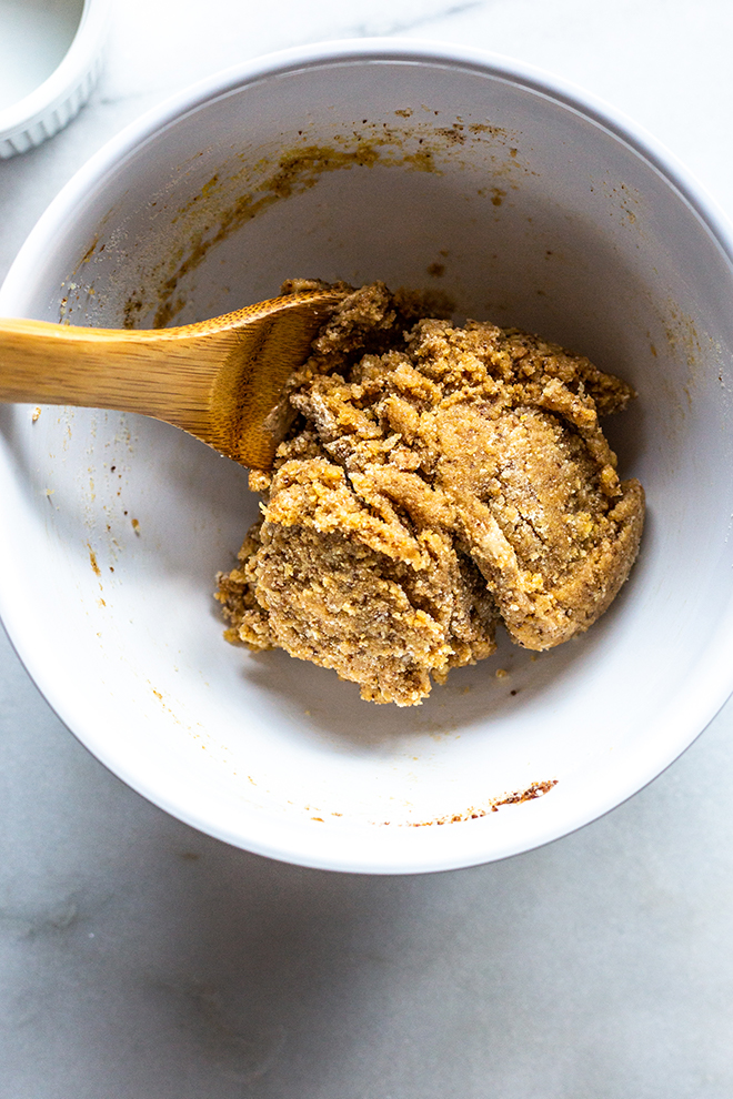 ingredients for paleo pie crust in a white bowl with a wooden spoon on a white marble background