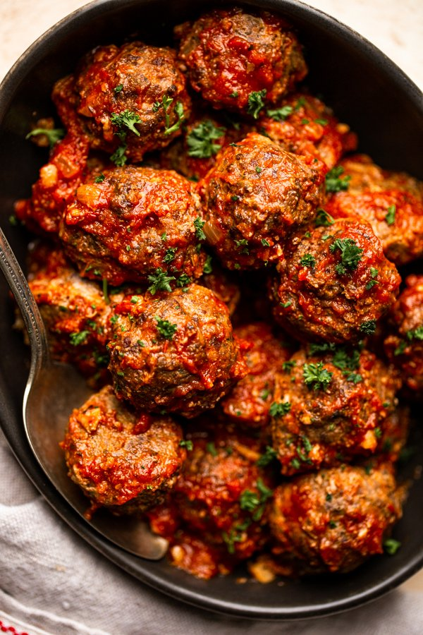 venison meatballs in a black bowl with red sauce