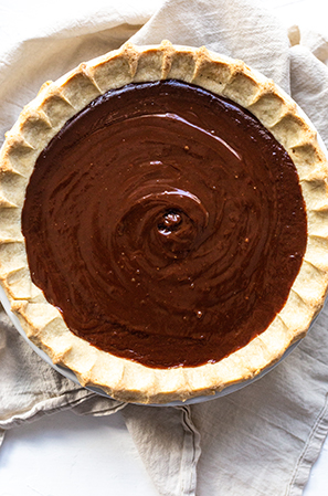 chocolate pie filling in a crust on a white background
