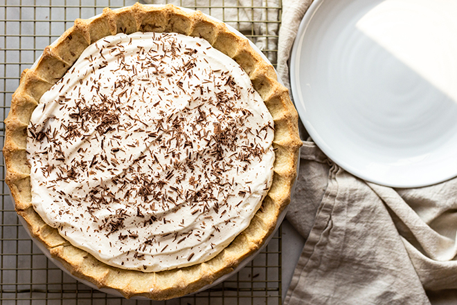 Whipped cream on a pie on a gold cooling rack with chocolate shavings
