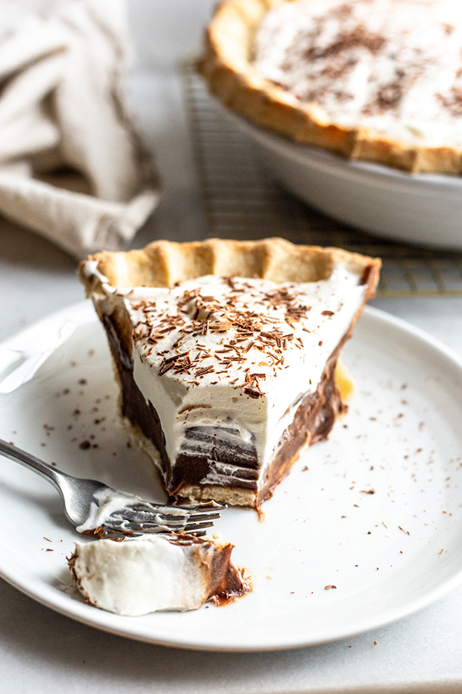 chocolate silk pie with whipped cream topping with a bite out of it