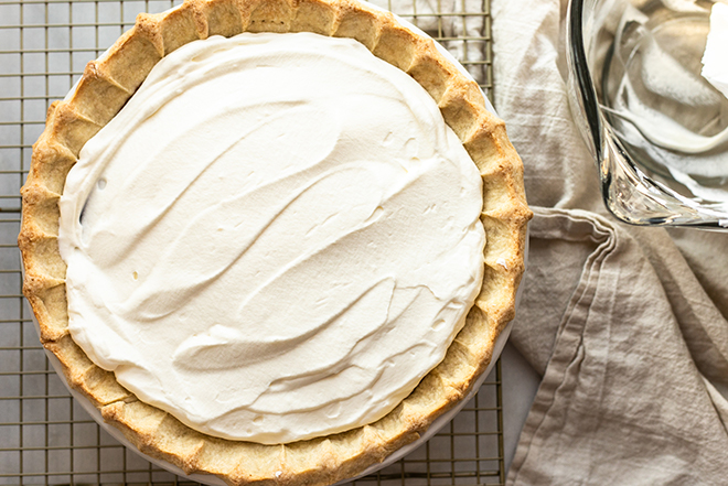 Whipped cream on a pie on a gold cooling rack