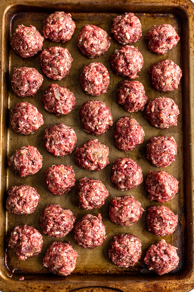 meatballs rolled on a gold baking sheet