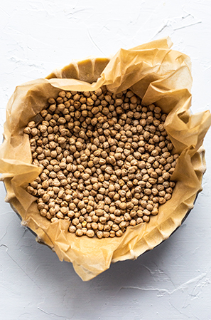 pie crust weighed down with chickpeas in parchment on a white background