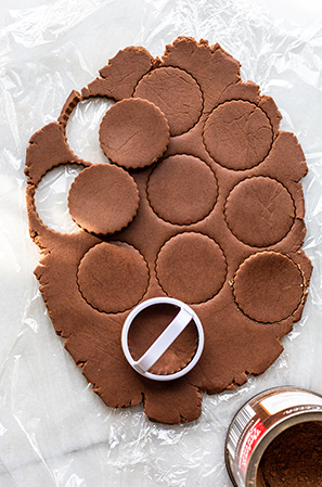rolled out chocolate cookie dough cut out into circles