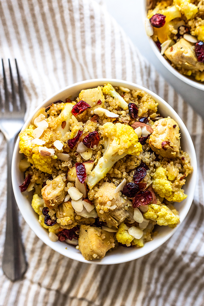 quinoa salad with cranberries cauliflower and chicken in a white bowl