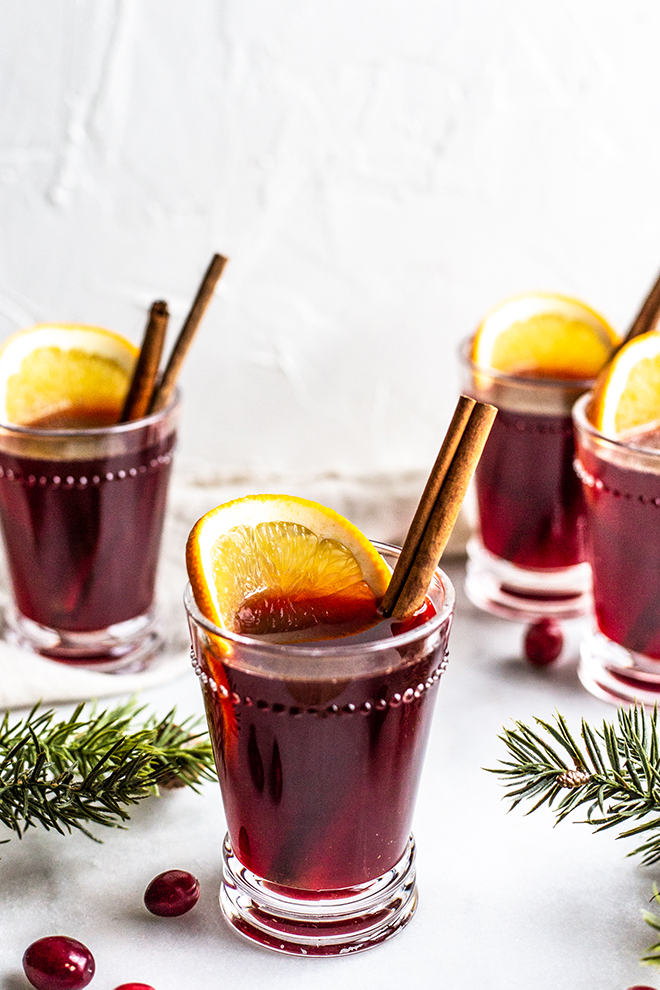 cups of mulled with with cinnamon on a white background