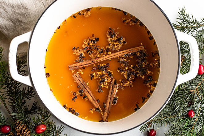 apple cider and mulling spices in a white pot with winter greens