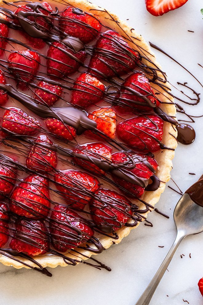 Fresh strawberries with hints of orange and vanilla fill a flakey tart crust and everything is covered in a chocolate drizzle.