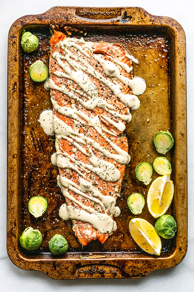 salmon drizzled with tahini sauce on a sheet pan with brussels and lemon