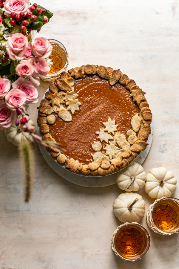 pumpkin pie on a cream board with pretty crust and pink flowers