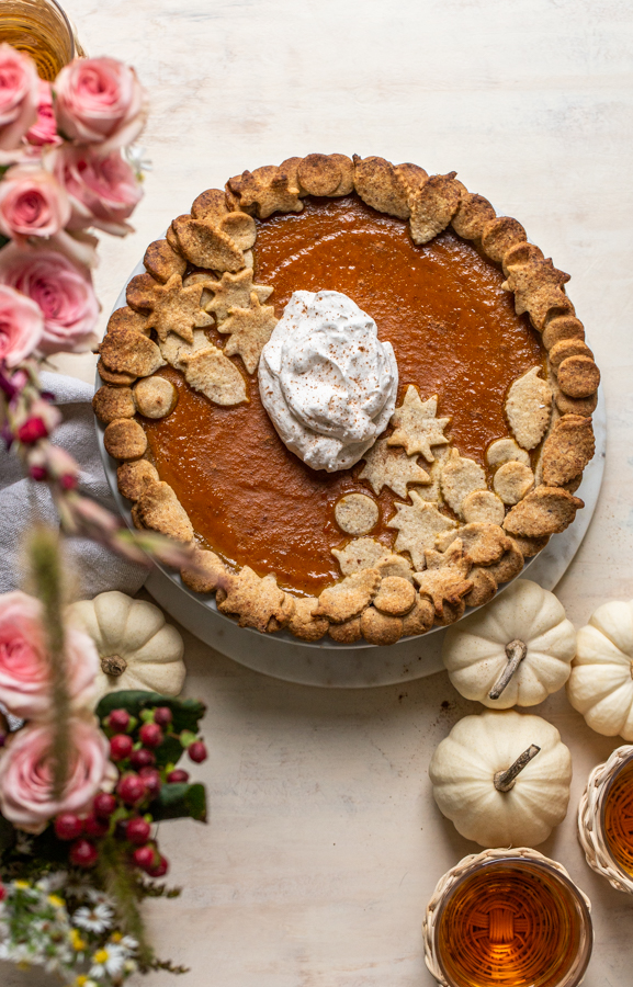maple bourbon pumpkin pie with pink flowers and whipped cream