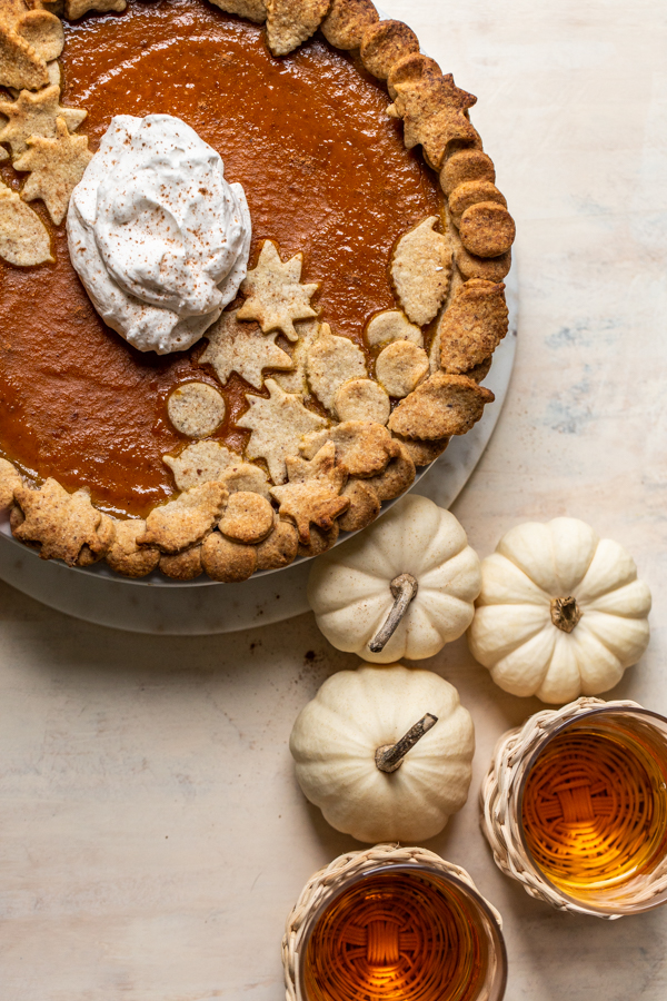 pumpkin pie with whipped cream and white pumpkins