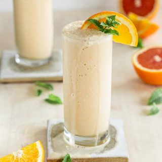 dairy free orange creamsicle milkshake in a slender glass with a coaster on a cream backdrop, mint and oranges