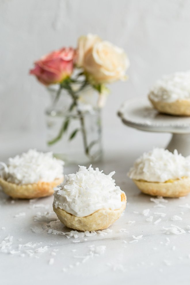 mini coconut cream pies with roses in the background on a white background.