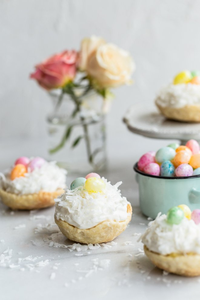 easy mini coconut cream pies with pastel jelly beans on marble with coconut on top and roses and a jelly bean bowl in the background