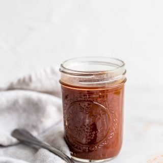 paleo BBQ sauce in a glass jar with a cream linen on a white background with a silver spoon