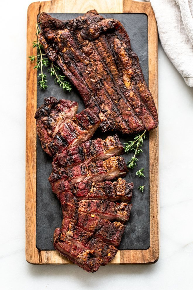 venison brisket on a wood cutting board with slate and thyme