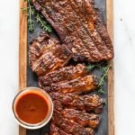venison brisket with barbecue sauce on a wood cutting board with slate