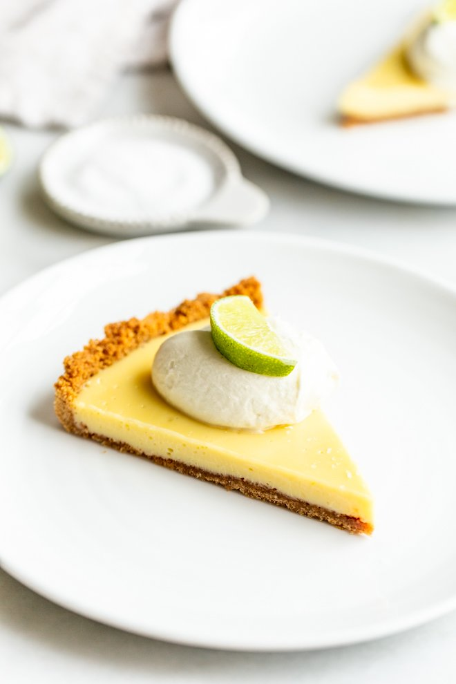 slice of key lime pie on a white plate with a dollop of whipped cream and a lime
