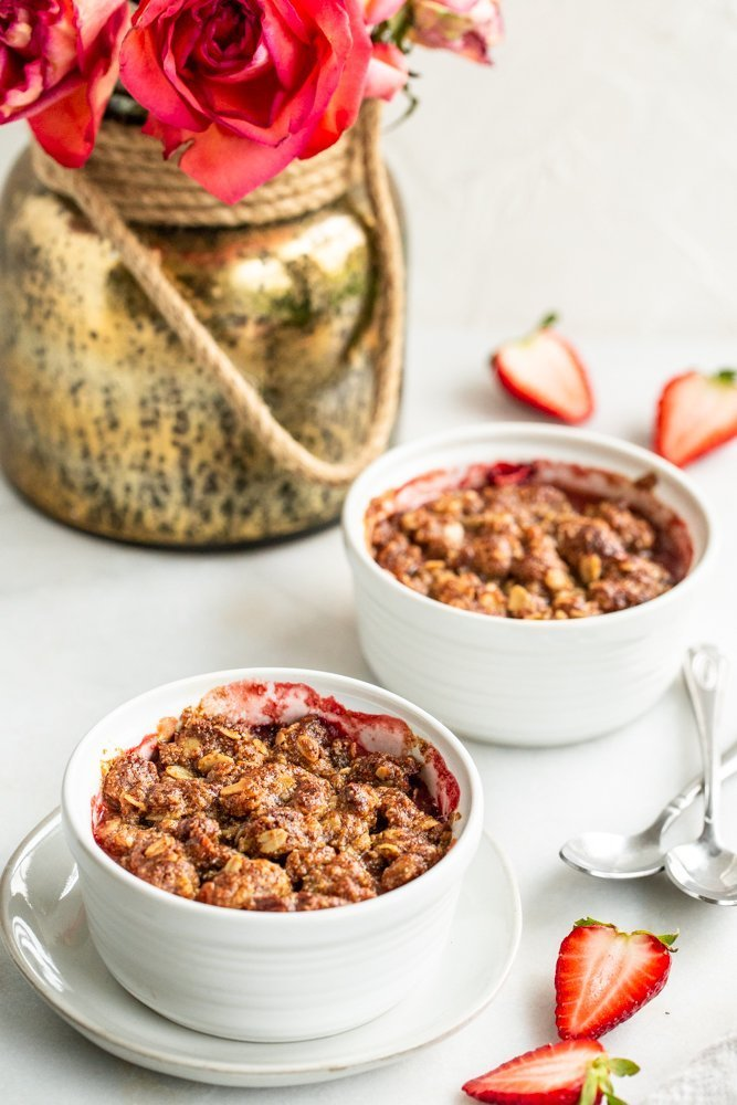 Gluten Free Strawberry Crisp for Two on a white background with strawberries on a white background