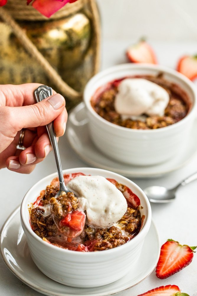 Gluten Free Strawberry Crisp for Two on a white background with strawberries on a white background with vanilla ice cream and a hand scooping in