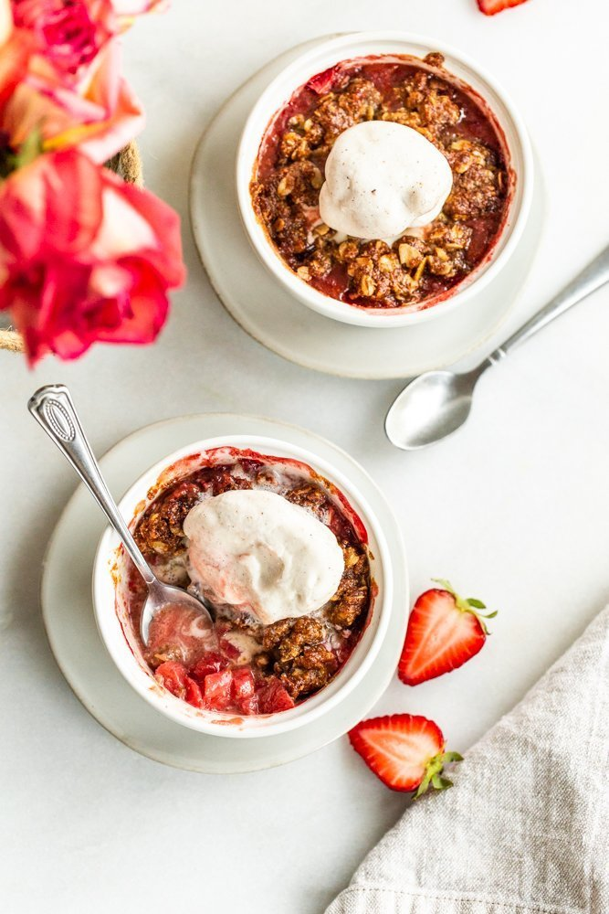 Gluten Free Strawberry Crisp for Two on a white background with strawberries on a white background with vanilla ice cream shot overhead