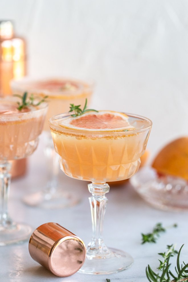 grapefruit cocktail with a grapefruit slice, a shaker cap, herbs on a white background
