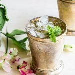 a mint julep cocktail with a glass of mint and flowers on a cream background