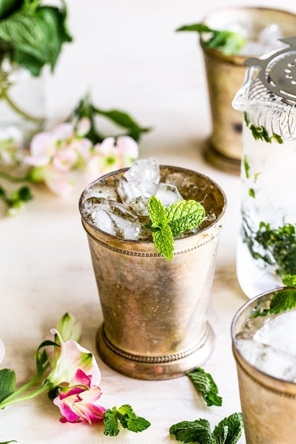 mint julep cocktail with mint garnish on a cream background with flowers