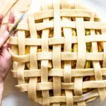 a lattice apple pie being made on a white background, unbaked